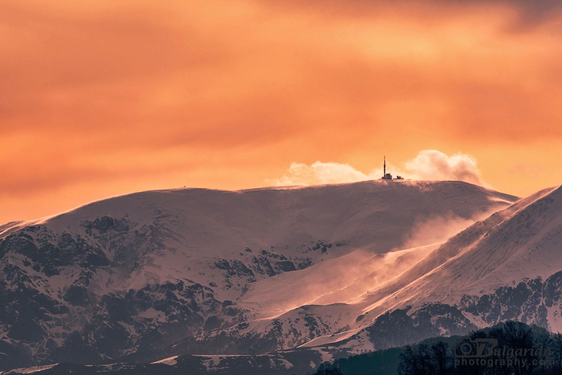 Връх Ботев. Кулата на върха в съчетание с облаците около нея прилича на излитаща ракета.