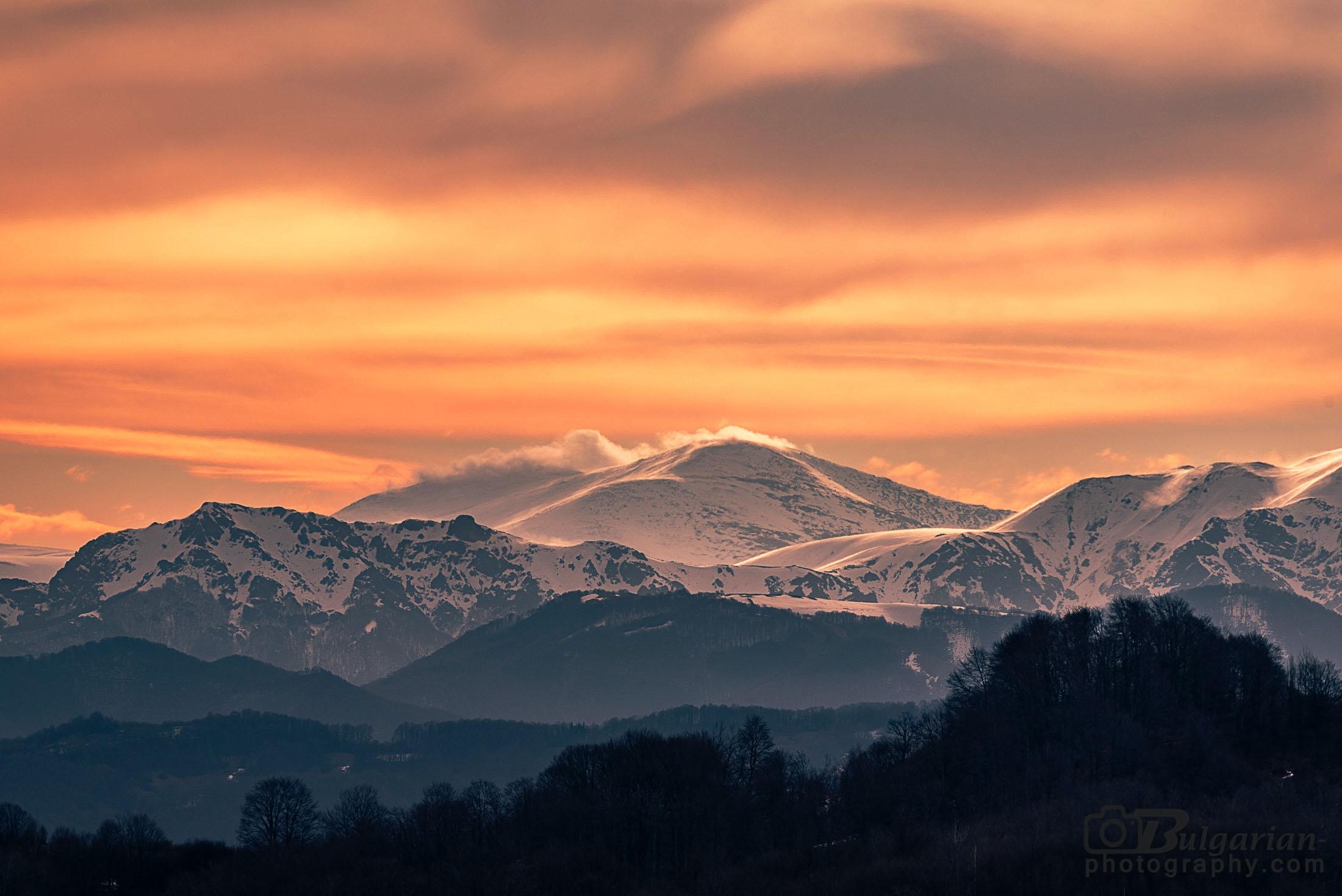 Връх Голям Кадемлия в облаците, а в ляво е връх Марагидик