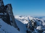 Отвесната сива скала под върха