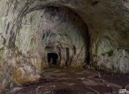 Деветашка пещера. Входът за сухият клон, виждат се и постаментите останали от петролните резервоари.